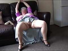 Matured granny with massive tits and hairy bush stripping and teasing